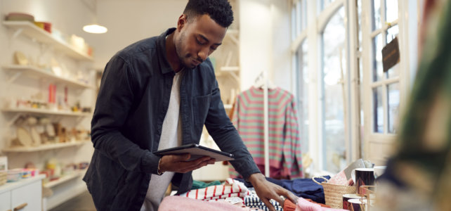 Small Business Owner Checks Stock In Shop Using Digital Tablet