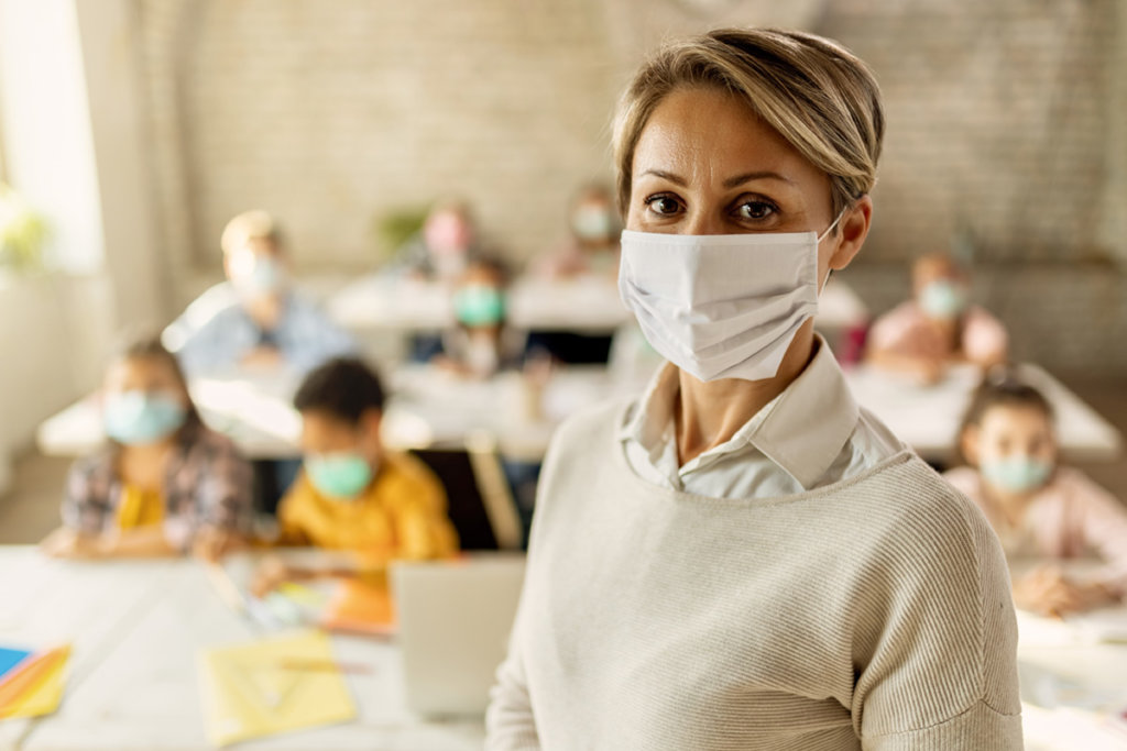 A female school teacher with protective face mask in the classroom.