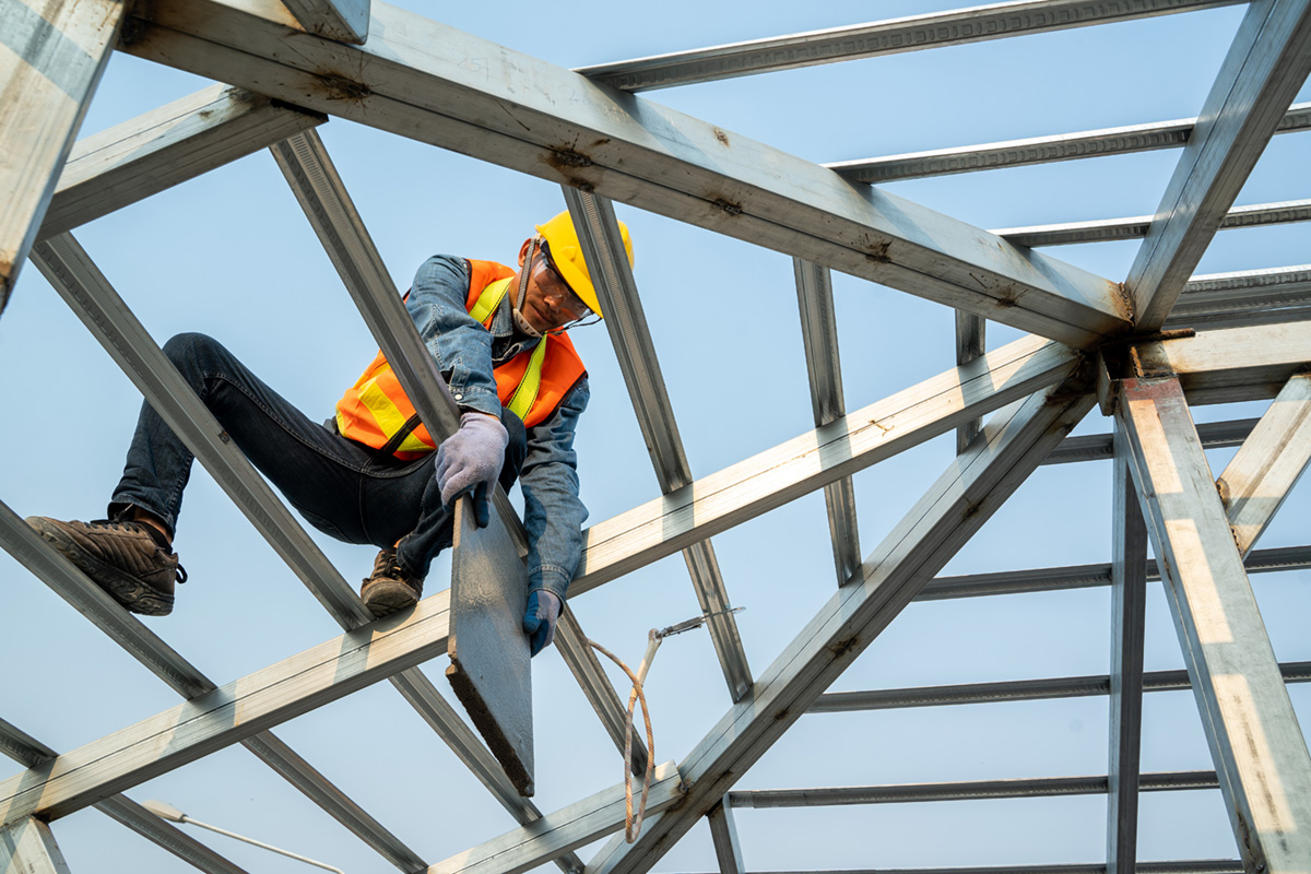 Photo of a construction worker wearing safety harness working in a high place.