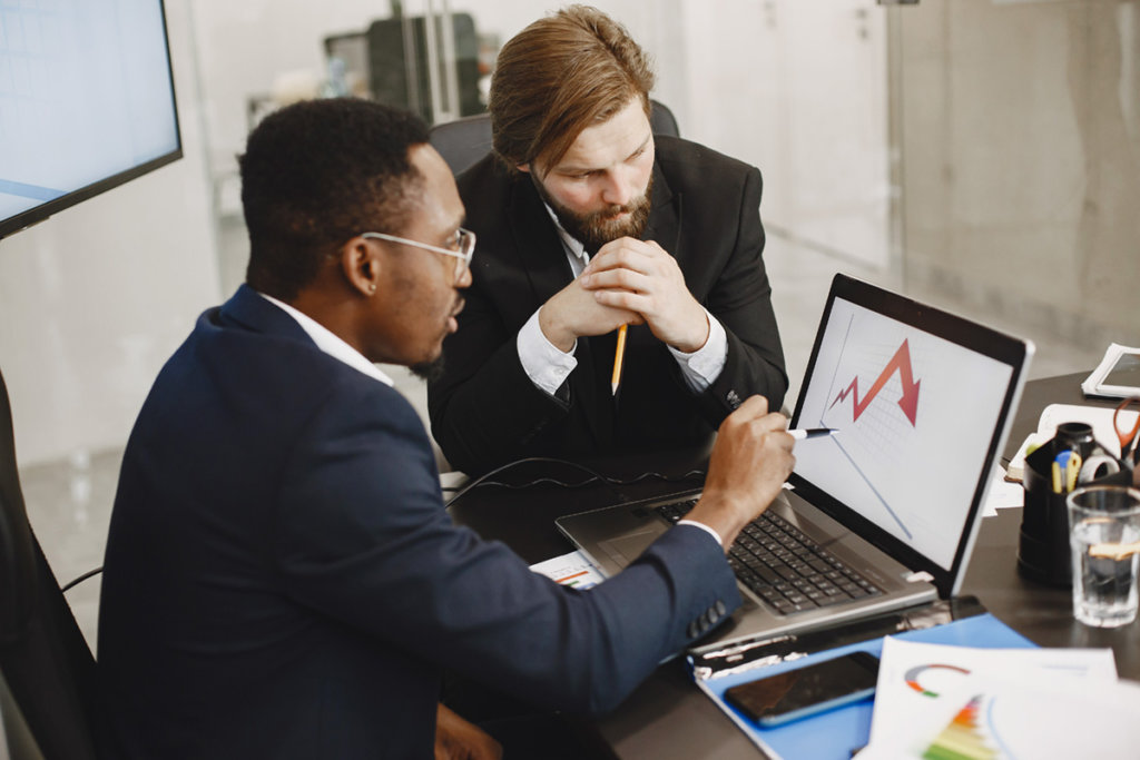 Two males in business suit reviewing a chart