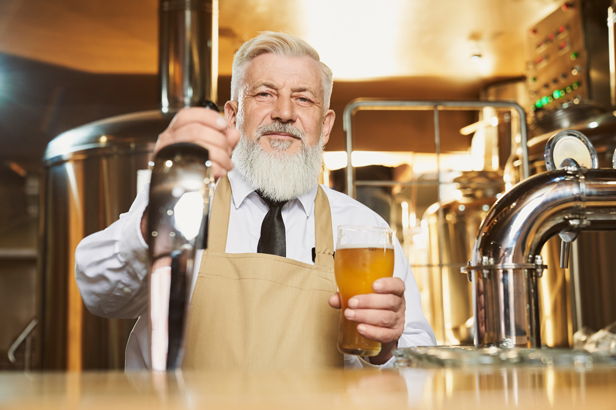 A brew master holding a beer at a brewery.