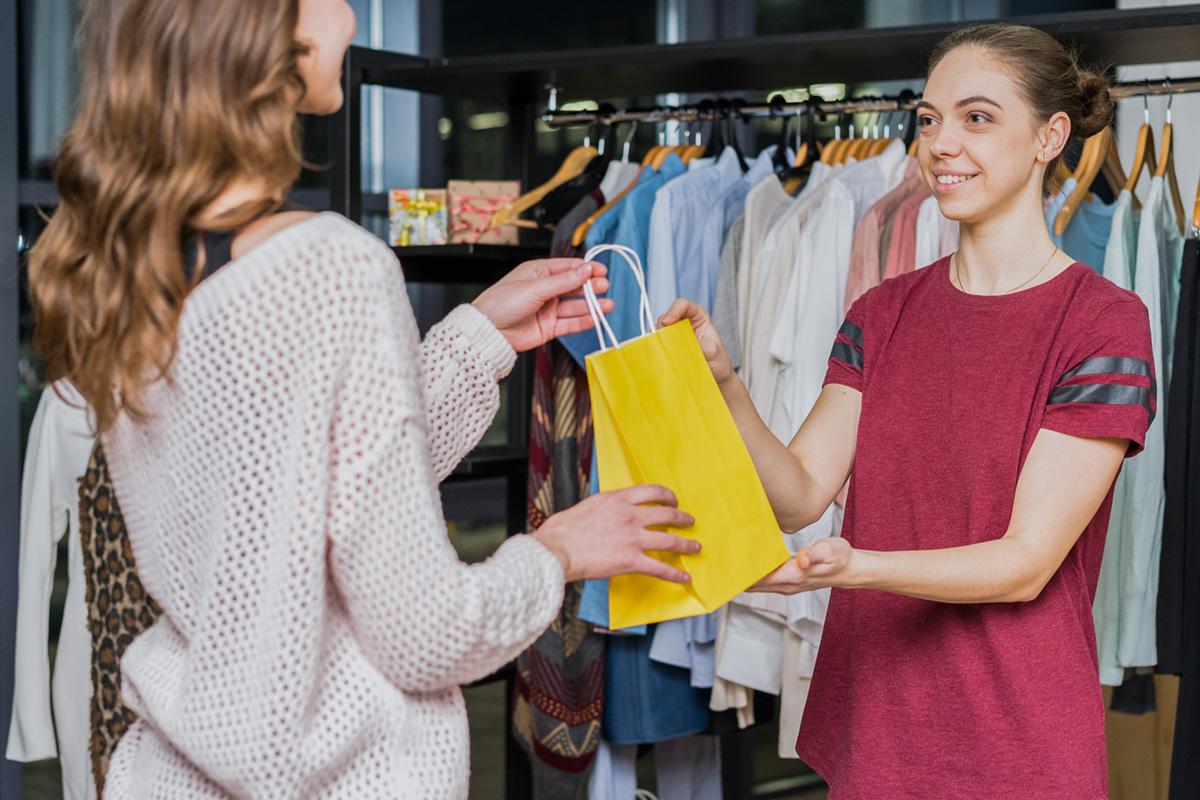 A female retailer handing a shopping bag to a customer.