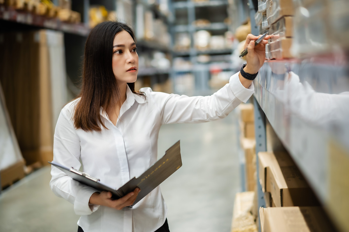 Female worker checking items at warehouse