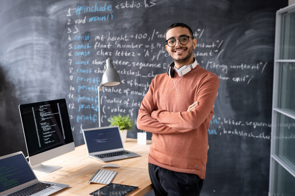 Young IT manager posing in front of a desk and laptop.